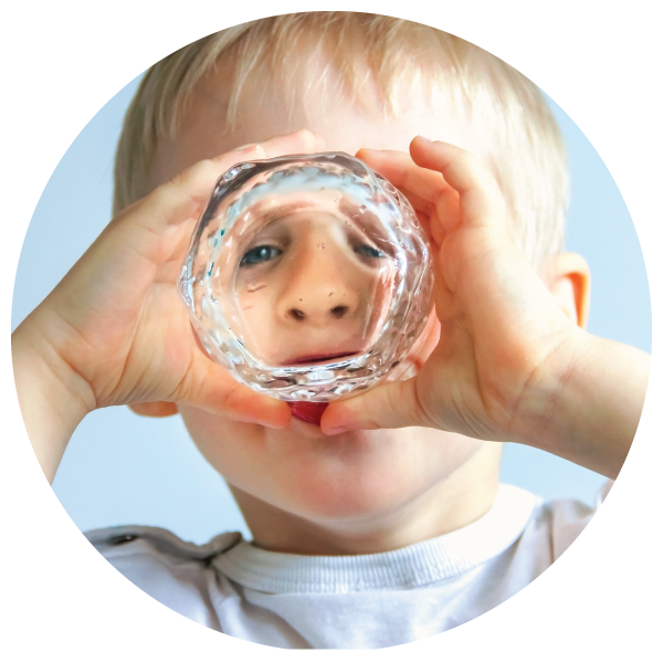 a toddler looks through the bottom of a glass while he drinks